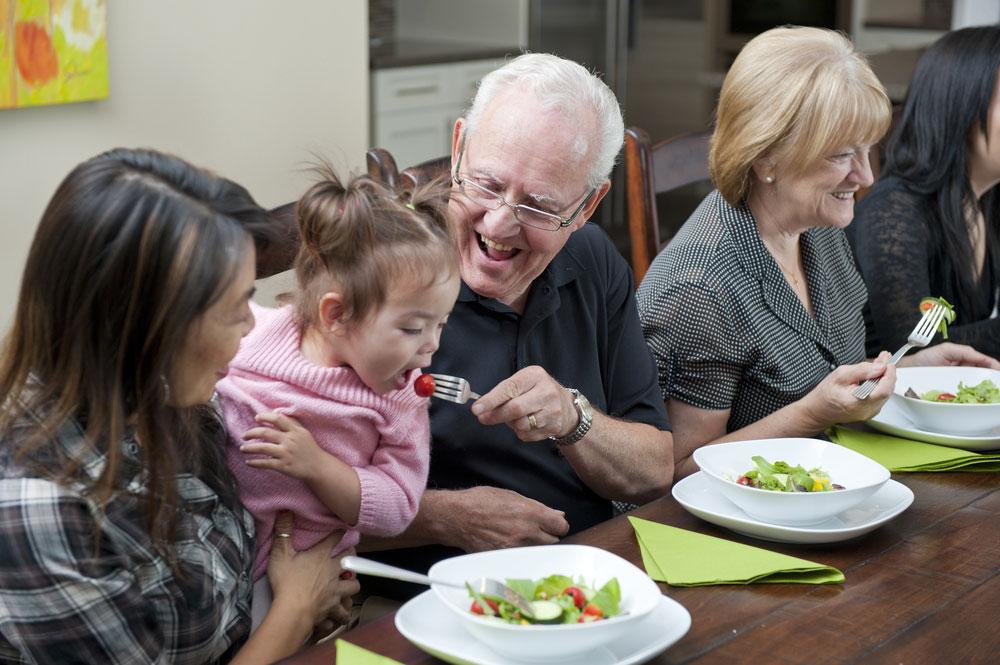 Grandpa feeding granddaughter at family reunion