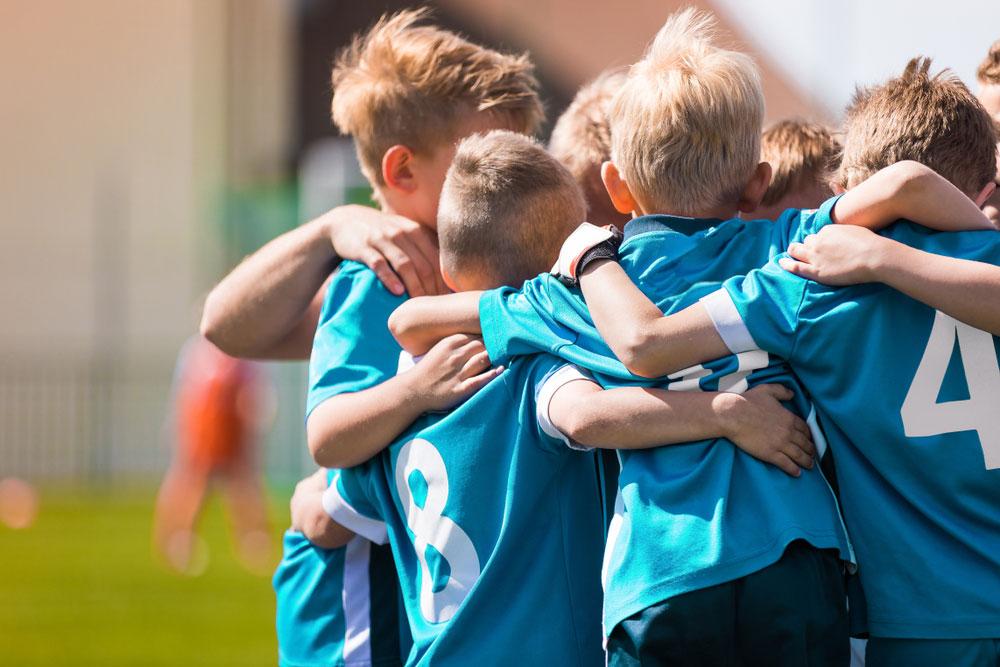 Boys in soccer jerseys huddled